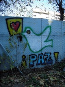 Image of dove carrying heart, and the word PAZ, painted on a wall in Madrid